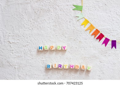 happy birthday - garland and letters on concrete background