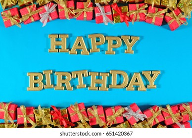 Happy birthday golden text and golden and red gifts on a blue background
