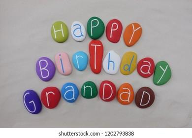 Happy Birthday Grandad with colored stones over white sand