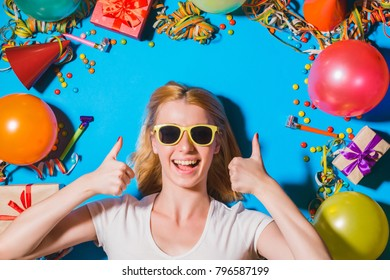 Happy birthday and holidays concept. Young woman in sunglasses showing big thumbs up, gift boxes and holidays accessories on blue background. Overhead view. Focus on woman face.