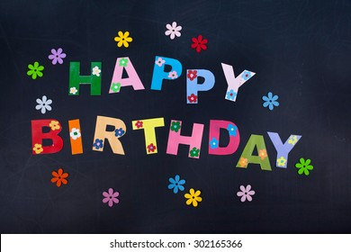 'Happy Birthday' letters on chalk board background, paper cut design.