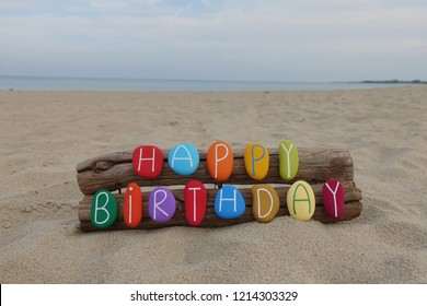 Happy Birthday message with a creative composition of colored stone letters on the beach