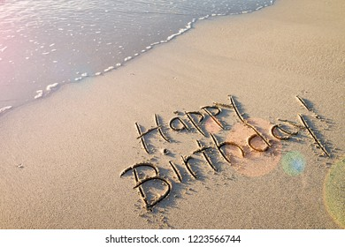 Happy Birthday! message handwritten in smooth sand with festive lens flare on the shore of an empty beach