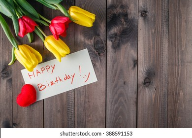 Happy birthday message and tulips flower on table