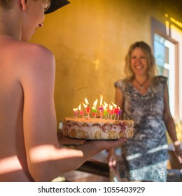 Happy birthday, mom. Teenage boy with baseball cap holding homemade birthday cheese cake with burning candles surprises his smiling mother outside the house. Real joy - emotion story at hot summer.