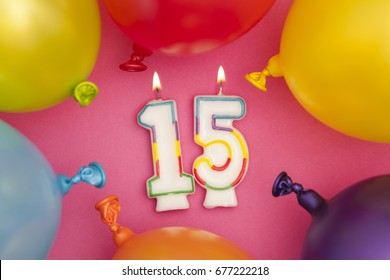 Happy Birthday number 15 celebration candle with colorful balloons