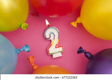 Happy Birthday number 2 celebration candle with colorful balloons