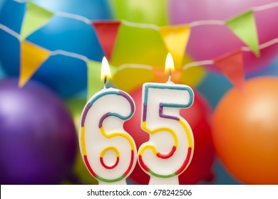 Happy Birthday number 65 celebration candle with colorful balloons and bunting