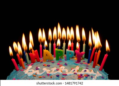 Happy Birthday on a cake full of candles isolated on black with copy space and a shallow depth of field