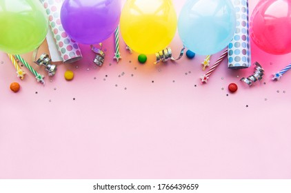 Happy birthday or party background.  Flat Lay wtih birthday balloons , confetti and ribbons on pink background. Top View.  Copy space.