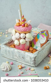 Happy Birthday party background: Freak shake topping with donut, marshmallow decorated as unicorn in the wooden box filled with popcorn; selective focus