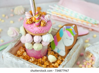 Happy Birthday party background: Freak shake topping with donut, marshmallow decorated as unicorn in the wooden box filled with popcorn; selective focus.