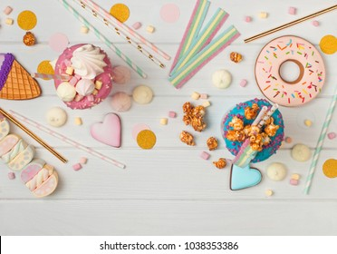 Happy Birthday party background with two freak shakes, donut, marshmallow, meringues, popcorn and marmalade on white wooden background with blank space for text; top view, flat lay