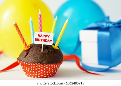 Happy birthday party card with a chocolate cupcake, candles, gift box and colorful balloons on background.