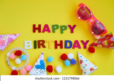Happy birthday party with glasses, hats, bracelet on yellow background with copy space