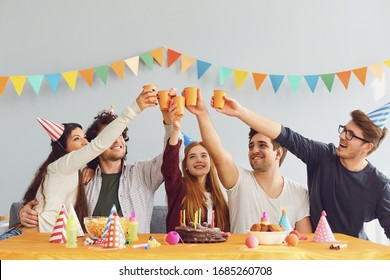 Happy Birthday party. A group of friends with a cake wishes the girl a happy birthday