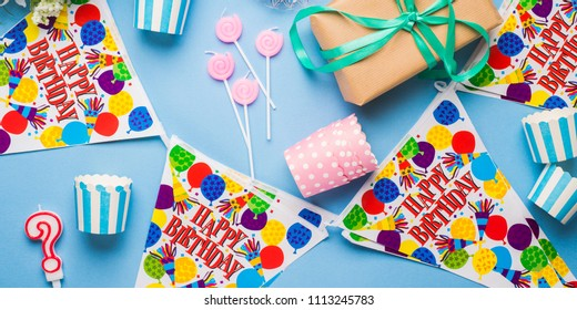 Happy Birthday party items flat lay. Candles, gift box, decoration banner, paper glasses, chocolate cake