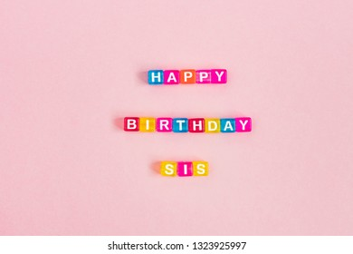 Happy birthday sis inscription made of colorful cube beads with letters. Festive pink background concept with copy space