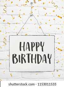 Happy birthday text. Banner on white brick background with golden party confetti. Celebrate date of birth.