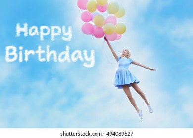 Happy Birthday text and beautiful young woman with colorful balloons against blue sky