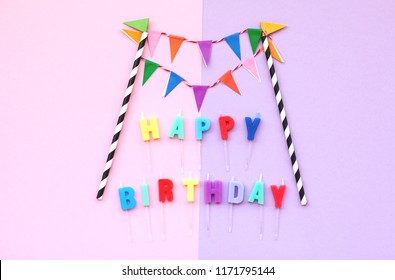 Happy Birthday text with colorful paper flags garland on pink, violet background. Festive backdrop for holidays: Birthday dayFlat lay style.