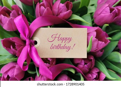 Happy birthday text on label in front of purple flowers - tulips.