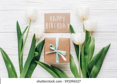 happy birthday text sign on greeting card with stylish present box and tulips on white wooden rustic background. flat lay mock up with flowers and empty paper with space for text