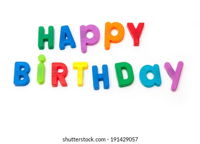 Happy Birthday written in magnetic letters isolated on a white studio background.