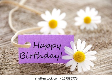 happy birthday written on a purple banner, flowery background