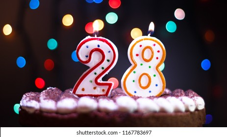 Happy Birthday.Holiday cake with candles.Birthday greetings.Greeting card.Colorful birthday candles.Twenty-eight years.Growing up.Abstract colorful background.Colorful bokeh.Top view.Stop motion.
