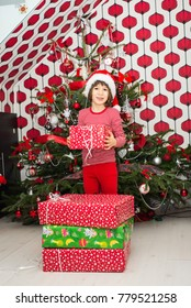 Happy biy four years old holding Christmas present in front of tree