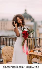 Happy black bride corrects her hair and smiling. Wedding day