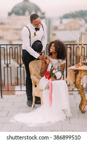 Happy black bride and groom smiling holding hands on the terrace. Wedding day