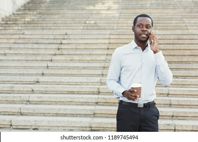 Happy black businessman talking on smartphone and drinking take away coffee outdoors. Young african-american salesman working with mobile, standing on the stairs in urban area cityscape