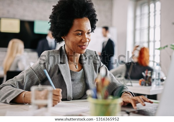 Happy black businesswoman working on a computer and writing notes at her office desk. There are people in the background.