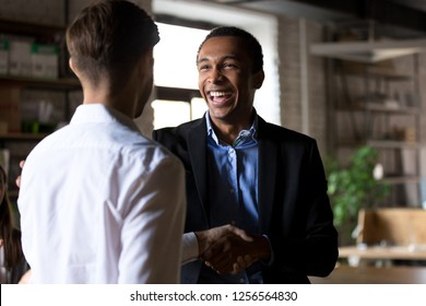 Happy black ceo handshaking rewarding successful worker, smiling african executive manager shaking hand congratulating employee promoting motivating for work achievement, respect recognition concept