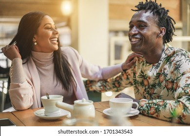 Happy black couple drinking tea at home during isolation quarantine - Young people having fun together during lockdown world situation - Domestic lifestyle concept - Focus on man face