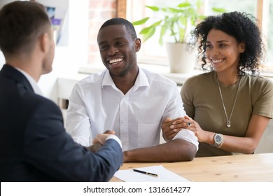 Happy black couple first time home owners handshaking realtor insurer landlord bank worker at meeting, african family customers make real estate deal for rent house purchase or mortgage investment