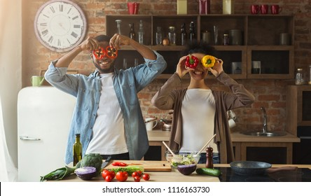Happy black couple having fun with colourful pepper in loft kitchen. Family preparing dinner