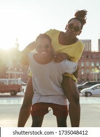 A happy black couple having fun in the city and riding piggyback.