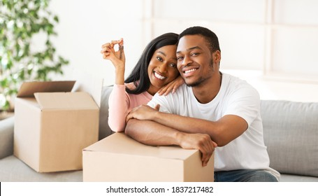 Happy black couple with house key and carton boxes looking at camera and smiling in their property, panorama. Young African American homeowners excited to move into new apartment