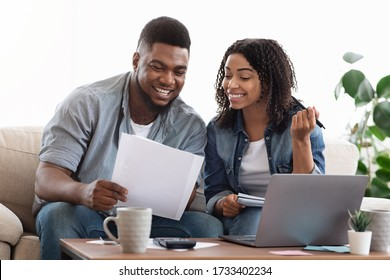Happy black couple reading financial documentation at home while planning family budget together, accounting their savings