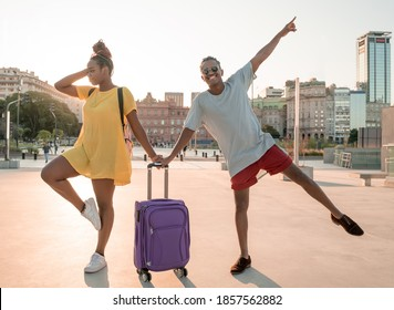 A happy black couple travelling with suitcases in the city.