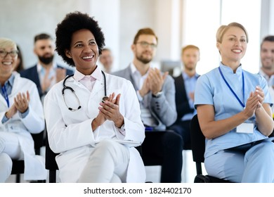 Happy black doctor and her colleagues clapping their hands after successful presentation in board room.