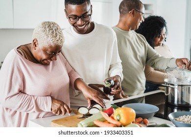 Happy black family cooking inside kitchen at home - Father, daughter, son and mother having fun preparing lunch - Main focus on boy face