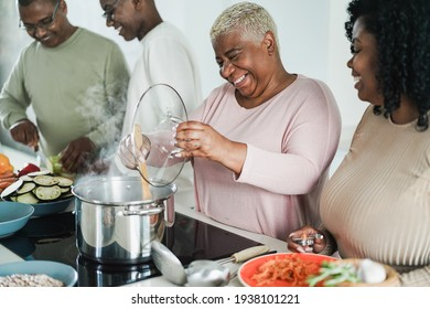 Happy black family cooking inside kitchen at home - Father, daughter, son and mother having fun preparing lunch - Main focus on mum face