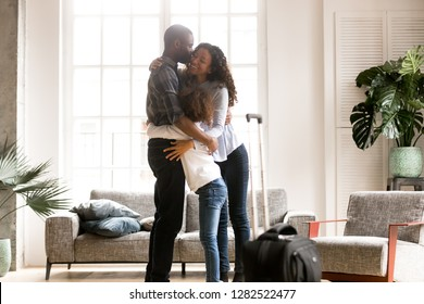 Happy black family embrace together in living room meeting welcoming african dad coming home after business trip with baggage, father hugs kissing wife and daughter after arrival, reunion concept