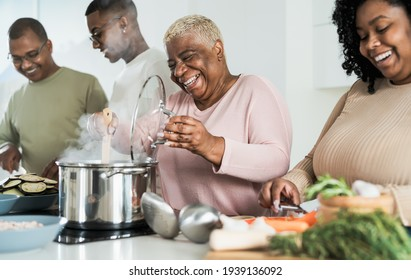 Happy black family having fun cooking together in modern kitchen - Food and parents unity concept  - Shutterstock ID 1939136092