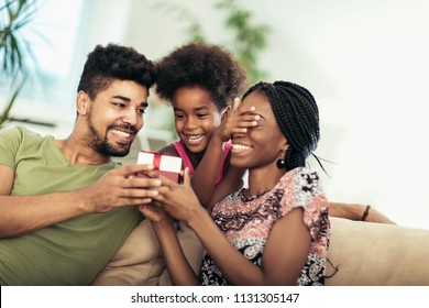 Happy black family at home. African american father, mother and child celebrating birthday, having fun at party. Daughter giving gift to mother