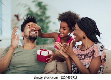 Happy black family at home. African american father, mother and child celebrating birthday, having fun at party.Daughter giving gift to father.